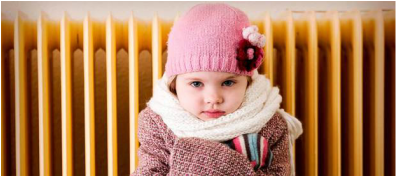 Image of a girl in a pink hat and scarf bundled up in front of a radiator.