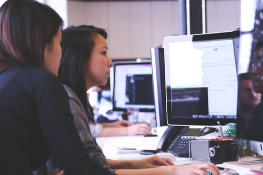 Image of two youth females sitting at a computer in a computer lab