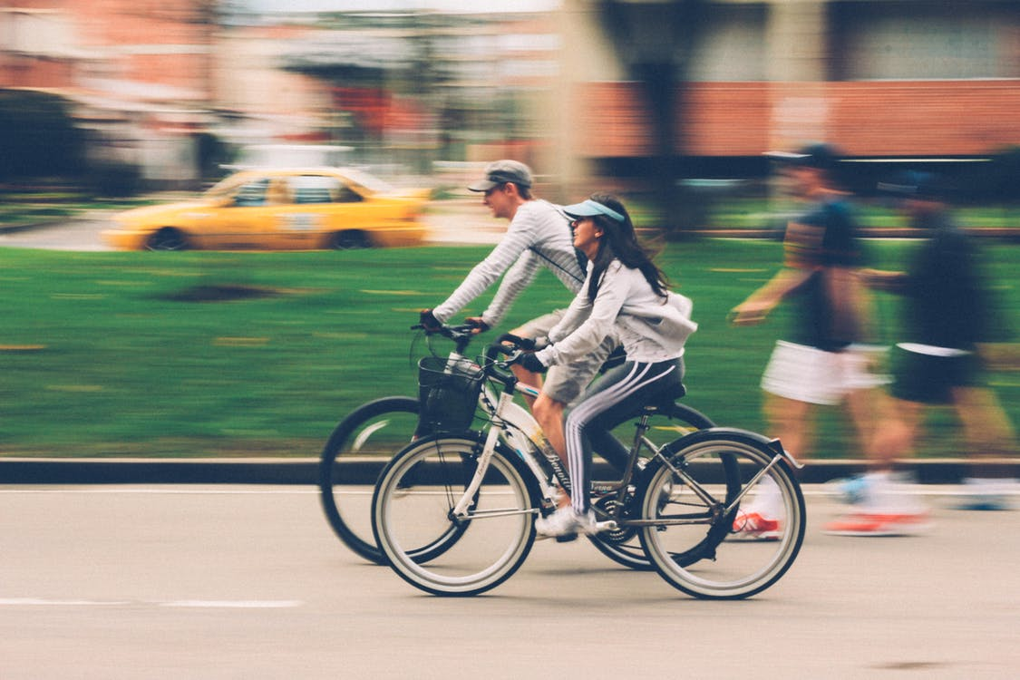Man and a woman riding their bikes in a city followed by two pedestrians