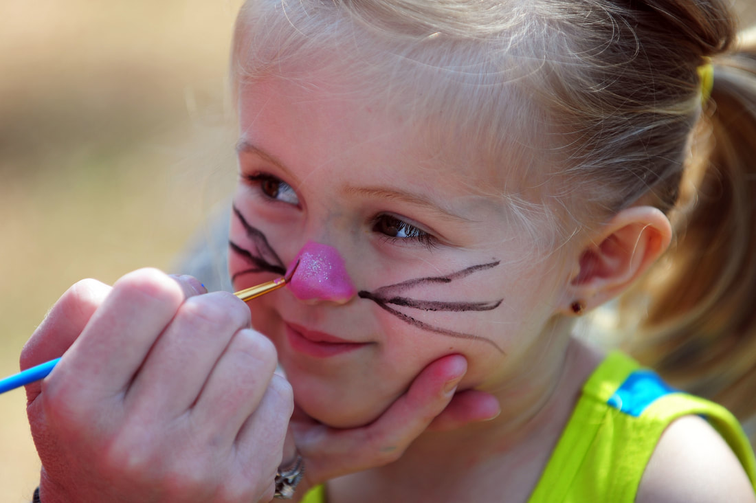 Child getting her face painted as a cat