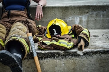 Image of a female firefighter with red fingernails sitting on a concrete step next to a helmet, coat and ax.