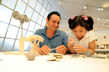 Man and young girl sculpting at the museum